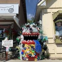 Un monstre fait d'objets recyclés est installé entre deux immeubles sur la rue.