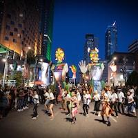 Des marionnettes géantes suivent une quinzaine de danseurs.