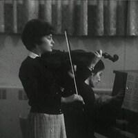 Jeune femme qui joue du violon, avec en arrière-plan une pianiste et une tourneuse de pages.