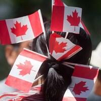 Une femme avec des drapeaux du Canada dans les cheveux.