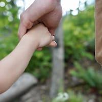 un papa marche main dans la main avec son enfant.