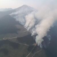 Vue aérienne d'un feu de forêt. On y voit beaucoup de fumée.