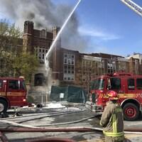 Des pompiers arrosent la façade d'un bâtiment