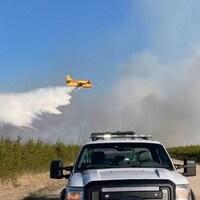 Un avion-citerne déverse de l'eau sur un feu de forêt.