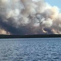 De la fumée épaisse s'échappe dans le ciel à l'horizon devant un lac.