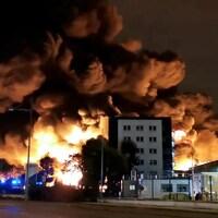 D'énormes flammes et de l'épaisse fumée émanent d'un édifice.