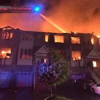 Les pompiers arrosent des maisons en flammes du haut d'une échelle.
