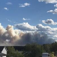 De la fumée derrière le toit d'une maison