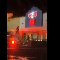 Des pompiers entrent dans l'épicerie la nuit.