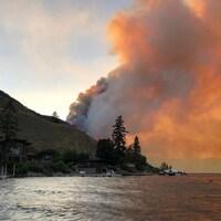 Des flammes brûlent derrière une colline.