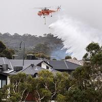 Un hélicoptère arrose des maisons.