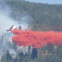 Des pompiers répandent des produits ignifuges sur un brasier près de Vernon, en Colombie-Britannique.