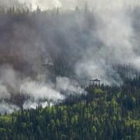 Des hélicoptères survolent une forêt d'où s'échappe de la fumée.