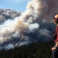 Un pompier regarde un incendie en train de ravager une forêt dans une montagne.