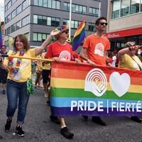 Des personnes marchent derrière une bannière de Centraide multicolore, sur laquelle il est écrit «fierté».