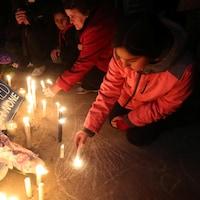 Une fille allume une chandelle à la place Mel-Lastman, de Toronto, lors de la vigile tenue en l'honneur des victimes de l'attaque au camion-bélier du 23 avril 2018.