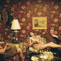 Deux femmes et un homme sont assis sur un sofa dans une pièce couverte de tapisserie fleurie.