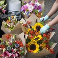 Une fleuriste ramasse des bouquets de fleurs avec des gants.