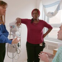 Les trois personnes parlent dans une salle d'hôpital blanche.