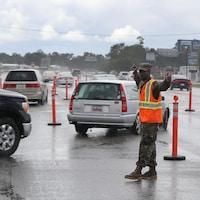 Plusieurs automobilistes sont dirigés par un officier de la garde côtière.