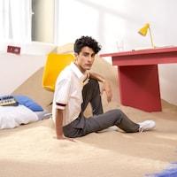 Le chanteur français Foé est assis de profil sur du sable, la jambe relevée, et regarde l'objectif.