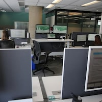 Deux personnes devant des ordinateurs.
