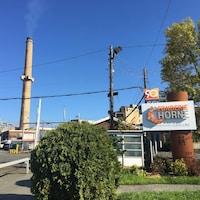 Panneau indiquant l'entrée de la fonderie Horne avec une cheminée de la fonderie derrière.
