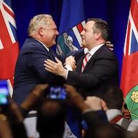 Le premier ministre de l'Ontario, Doug Ford, et le chef du Parti conservateur uni de l'Alberta, Jason Kenney (à gauche) se félicitent autour de deux drapeaux lors d'un rassemblement contre la taxe carbone à Calgary.