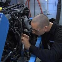 Un homme répare un moteur. Il porte des lunettes de protection.