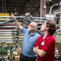 Un enseignant et son étudiant dans une usine.