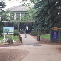 Vue extérieure d'un bâtiment, et de deux panneaux d'accueil pour les visiteurs.