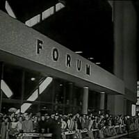 Foule massée derrière un cordon de sécurité à l'entrée du Forum de Montréal.