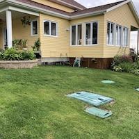 Une résidence secondaire et des couvercles qui recouvrent des installations septiques au sol.