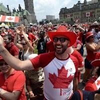Des gens habillés de rouge et blanc agitent des drapeaux du Canada sur la colline du Parlement.