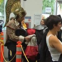 Plusieurs personnes, dont certaines portant un déguisement, font la file devant la caisse.