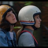 Les deux femmes sont sur un scooter et portent un casque.