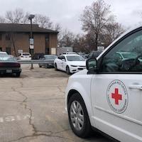 Une fourgonnette de la Croix-Rouge est stationnée dans un stationnement.