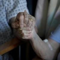 Un couple âgé se tient par la main dans un hôpital à Cambridge, en Grande-Bretagne, le 21 mai 2020.