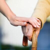 Une préposée aux soins tient la main d'une personne âgée.