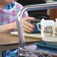 Gros plan sur la main d'une dame âgée qui tient un bol de nourriture.