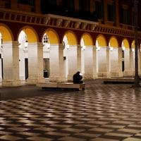 Un homme est assis sur un banc d'une place publique à Nice, en France.