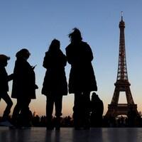 Des gens se tiennent sur la place du Trocadéro près de la Tour Eiffel à Paris.
