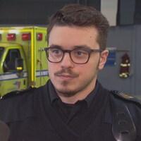Un jeune ambulancier en entrevue devant une ambulance