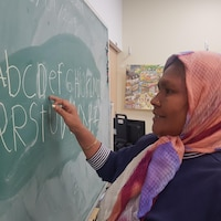 Une femme immigrante en train d'écrire au tableau d'une classe