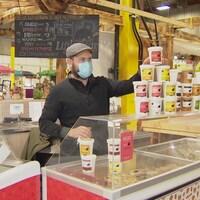 Franck Bouilhol place des pots de crème glacée sur son stand au marché fermier Bountiful.