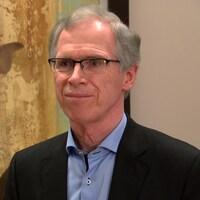 Le Dr François Desbiens, souriant, porte des lunettes et un veston foncé