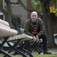 François Geoffroy assis sur un banc dans un parc.