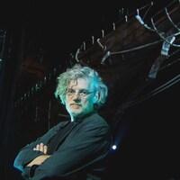 François Girard les bras croisés devant un vaisseau sur une scène.