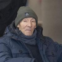 Un homme en fauteuil roulant avec une tuque et un manteau