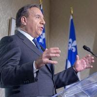Le premier ministre François Legault devant un micro, avec en arrière-plan deux drapeaux du Québec.